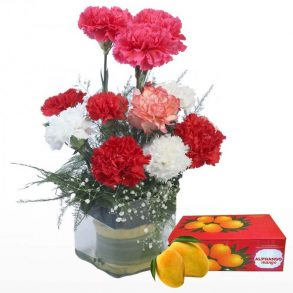 Red and white carnations placed in a square glass, and a box of mangos