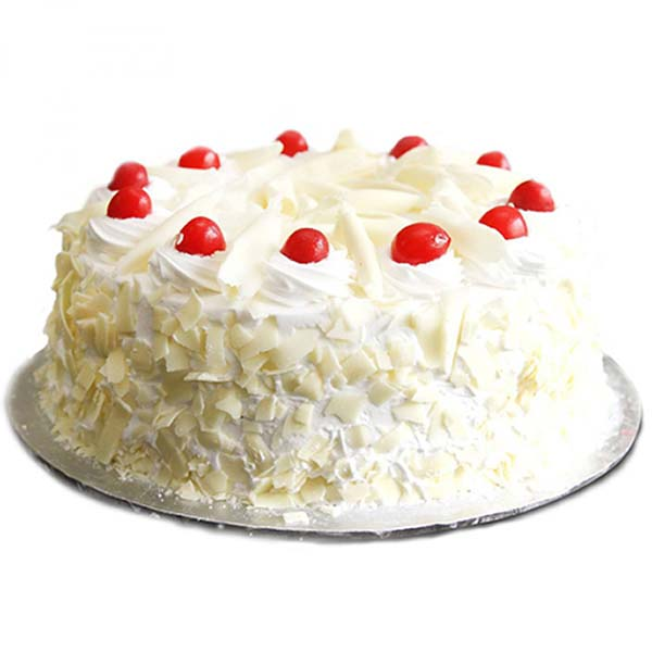 Round shaped white forest cake with red cherries on top