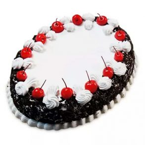 oval shaped black forest cake decorated with white cream and red cherries