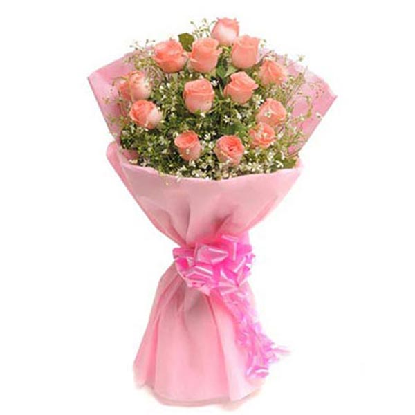 Pink roses and seasonal green leaves wrapped with pink paper and tied with pink paper and tied with pink ribbon