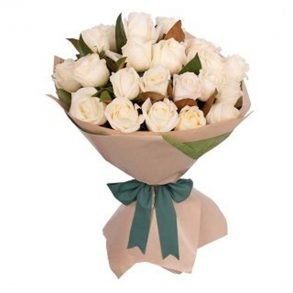 White roses wrapped in off white paper and tied with green ribbon