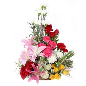 Basket arrangement of roses, carnations and lilies decorated with green leaves
