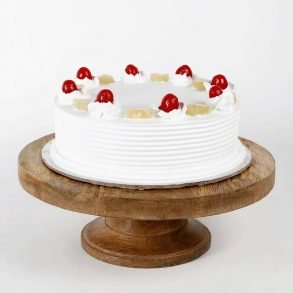 Round shaped white pineapple cake decorated with pineapple pieces and cherries on top