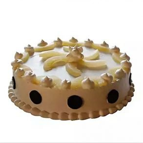 Round shaped pineapple cake decorated with white cream and pineapple pieces