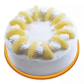 A round shaped white pineapple cake with pineapple slices on top