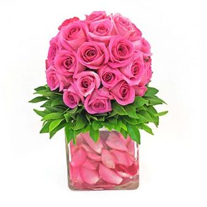 Pink roses decorated with green leaves placed in a square grass vase