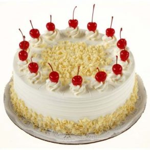 Round shaped white forest cake with cherries on top
