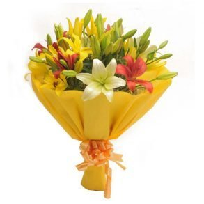 Colorful asiatic lilies wrapped in yellow paper and tied with yellow ribbon