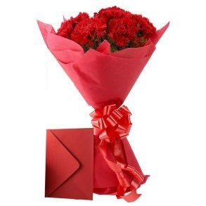 red carnations wrapped in red paper and tied with red ribbon, and a greeting card