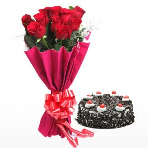 Red roses wrapped in red paper and tied with red ribbon, and a round shaped black forest cake