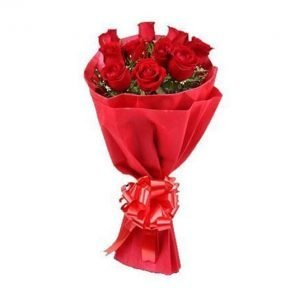 Bunch of red roses wrapped with red paper and tied with red ribbon