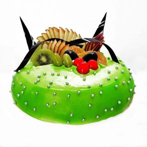 Round shaped pineapple cake decorated with green jelly, silver pearl and fruit slices