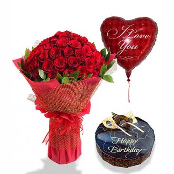 Red roses wrapped in red paper and a round shaped chocolate cake and heart shaped balloon