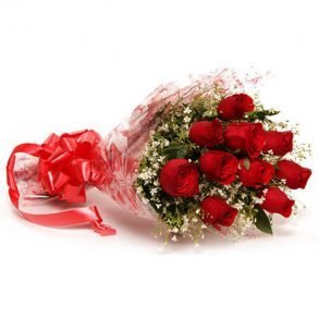 Red roses and seasonal green leaves wrapped with cellophane
