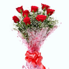 Red roses with seasonal small white flowers wrapped in pink cellophane