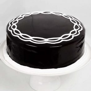 Round shaped chocolate cake decorated with white cream on top