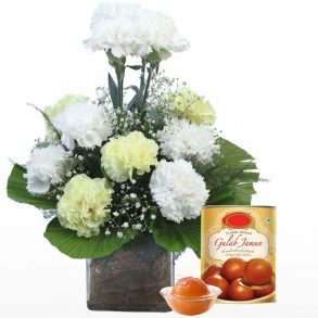 White carnation decorated with green leaves and gulab jamun