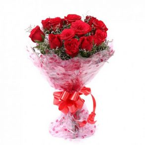 Red roses with seasonal green leaves wrapped in pink cellophane