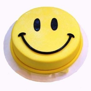 Round shaped yellow smiley cake with its smiling face