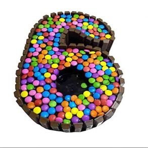 Six number shaped kit kat cake decorate with chocolate bars on side and colourful gems on top