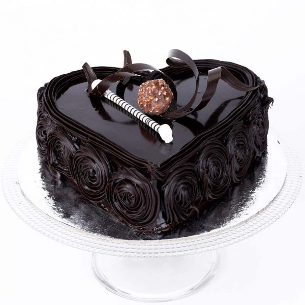 Heart shaped dark chocolate cake decorated with chocolate ball and crust on top and flower design on side