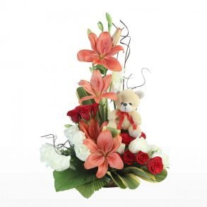Lilies and red roses decorated with green leaves and teddy