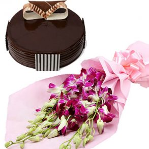 Purple orchids wrapped in pink paper, and round shaped chocolate cake