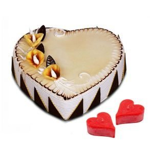 Heart shaped strawberry cake decorated with white cream and chocolates