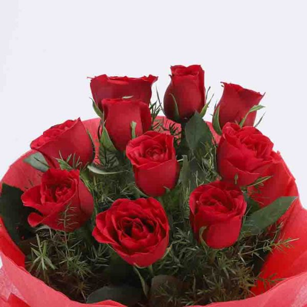 10 red roses with small green leaves wrapped in red paper