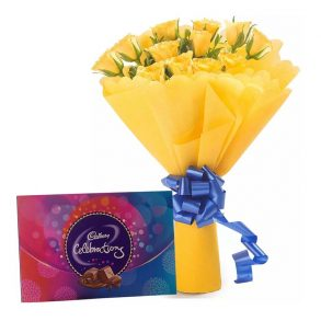 12 yellow roses wrapped in yellow paper and tied with blue ribbon with cadbury celebration box