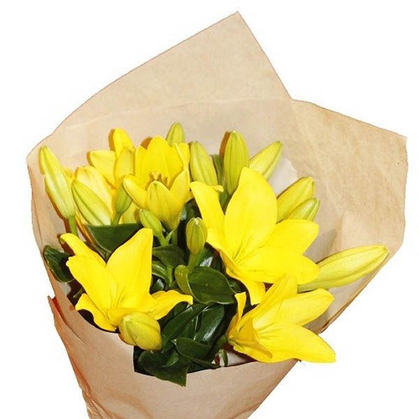 Yellow lilies wrapped in brown paper