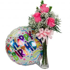 Pink roses and green leaves in a glass vase, and happy birthday balloon