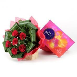 Six red roses and seasonal green leaves wrapped with red paper, and cadbury celebration box