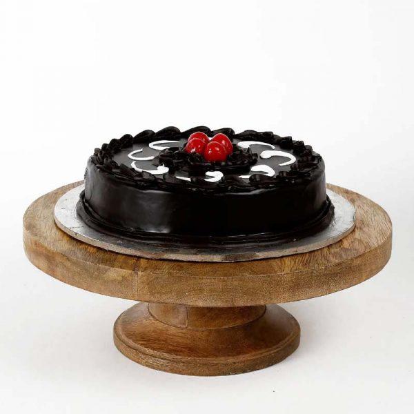 Round shaped chocolate truffle cake decorated with dark chocolate cream and cherries