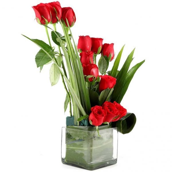 12 red roses decorated with green leaves in a square glass vase