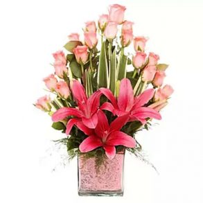 20 pink roses and 3 pink lilies decorated with green leaves in a square glass vase