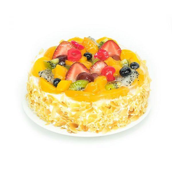 Round shaped walnut fruit cake decorated with fresh fruits