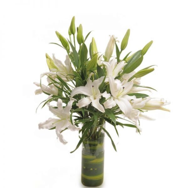 White lilies decorated with green leaves in round shaped glass vase