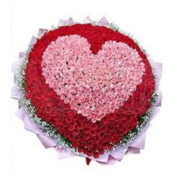 Pink and red roses designed as hearth and wrapped in pink paper