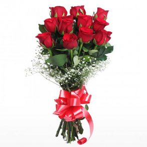 Long stem red roses and seasonal green leaves tied with red ribbon