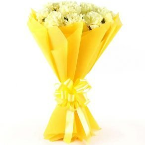 White carnations wrapped in yellow paper and tied with yellow ribbon