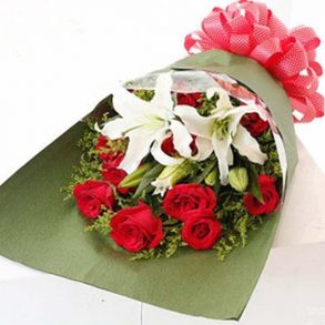 Red roses and white lilies wrapped in green paper and tied with pink ribbon